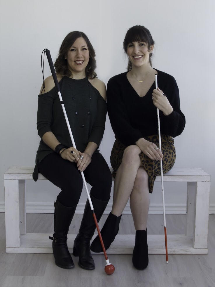 Natalie and Sarina are seated on a white bench with a white background. They are holding their canes in front of them and smiling.